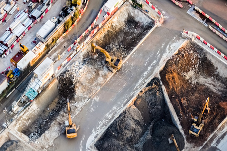 excavator: Aerial view excavators and tipper trucks working at construction. Hong Kong