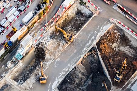 hong kong: Aerial view excavators and tipper trucks working at construction. Hong Kong