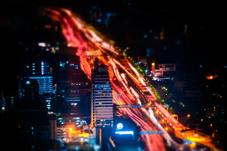 skyscraper skyscrapers: Tilt shift blur effect. Futuristic night cityscape aerial view panorama with illuminated skyscrapers and city traffic across streets. Bangkok, Thailand Stock Photo