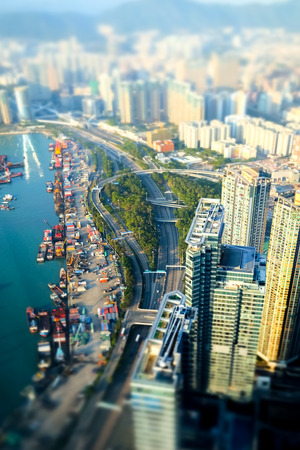 tilt and shift: Tilt shift blur effect. Aerial view of Hong Kong Island with port terminal at Victoria Harbor. Abstract futuristic cityscape with skyscrapers