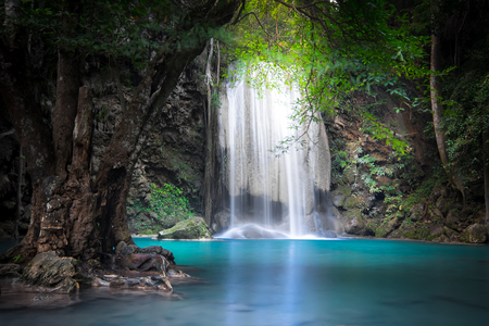 waterfalls: Jangle landscape with flowing turquoise water of Erawan cascade waterfall at deep tropical rain forest. National Park Kanchanaburi, Thailand