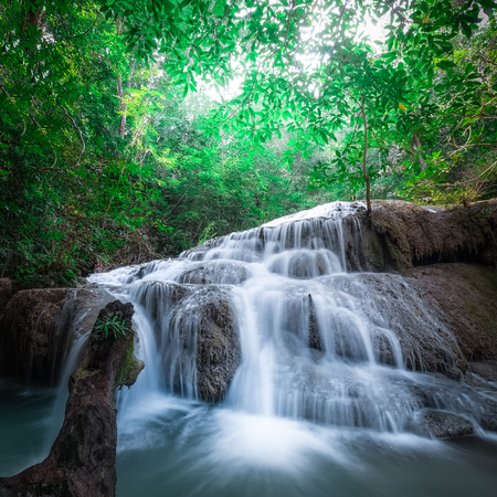 cascade: Jangle landscape with flowing turquoise water of Erawan cascade waterfall at deep tropical rain forest. National Park Kanchanaburi, Thailand