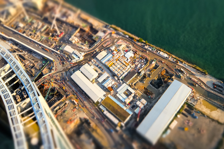 commercial building: Tilt shift blur effect. Aerial cityscape view with building construction near the harbor. Hong Kong. Abstract futuristic cityscape Stock Photo