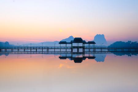 Tilt shift blur effect. Amazing park landscape panorama at sunrise. Bridge and pavilion on lake at Hpa-An, Myanmar (Burma) travel landscapes and destinations Stock Photo