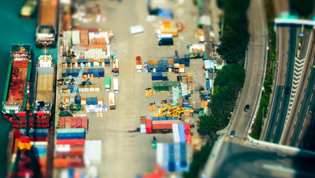 tilt shift: Tilt shift blur effect. Aerial view cargo ships loaded by crane with cargo containers at a busy port terminal. Hong Kong