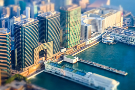 tilt shift: HONG KONG - JAN 22, 2015: Tilt shift effect. Aerial view of Hong Kong Island with port terminal. Modern financial and cultural city at Victoria Harbor Futuristic cityscape with modern skyscrapers