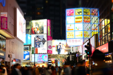 HONG KONG: HONG KONG - JAN 16, 2015: Night view of big sopping mall with bright illuminated banners and people walking on crossroad at crowded city. Hong Kong Editorial