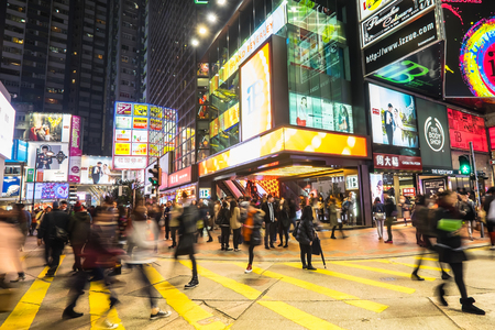 HONG KONG - JAN 16, 2015: Night view of big sopping mall with bright illuminated banners and people walking on crossroad at crowded city. Hong Kong Редакционное