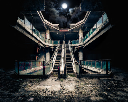 moonlight: Dramatic view of damaged escalators in abandoned building. Full moon shining on cloudy night sky through collapsed roof. Apocalyptic and evil concept