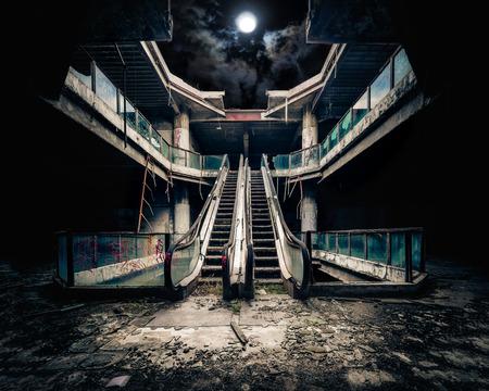 Dramatische mening van beschadigde roltrappen in verlaten gebouw. Volle maan schijnt op bewolkte hemel door ingestorte dak. Apocalyptische en kwaad begrip