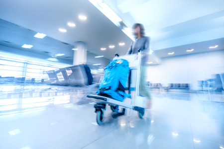 travel woman: Abstract blurred image of traveling woman in airport terminal pushing luggage cart. Art toning. Travel concept background Stock Photo
