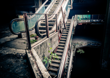 Dramatic view of damaged escalators in abandoned building. Apocalyptic and evil concept Standard-Bild