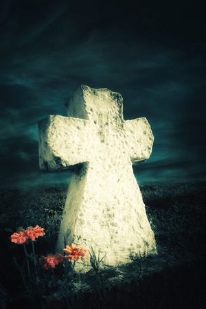 near death: Dark night spooky landscape with flowers growing near abandoned grave memory stone  under dramatic sky. Evil and death concept