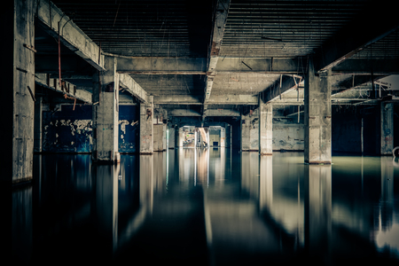 Dramatic view of damaged and abandoned building sunken by rain flood waters. Apocalyptic and evil concept