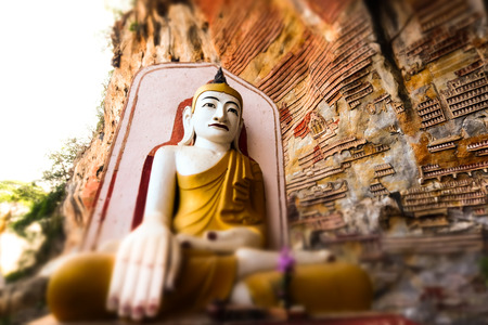 goon: Tilt shift blur effect. Amazing view of lot Buddhas statues and religious carving on limestone rock in sacred Kaw Goon cave. Hpa-An, Myanmar (Burma) travel landscapes and destinations