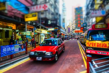 tilt view: HONG KONG - JAN 15, 2015: Hong Kong cityscape view with city transport and plenty bright advertisements, billboards on skyscrapers facades. Tilt shift lens blur