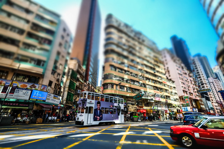 tilt and shift: HONG KONG - JAN 15, 2015: Hong Kong cityscape view with city transport and plenty bright advertisements, billboards on skyscrapers facades. Tilt shift lens blur