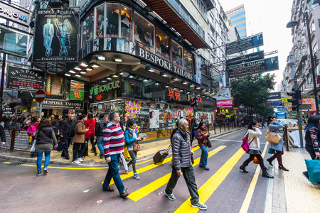 street life: HONG KONG - JAN 18, 2015: Hong Kong cityscape view. People walking on crossroad at crowded streets with skyscrapers and shopping malls