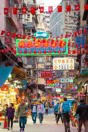HONG KONG - 18 januari 2015: Cityscape van Hongkong oog met veel heldere advertenties en billboards. Mensen lopen op drukke straten met wolkenkrabbers en winkelcentra