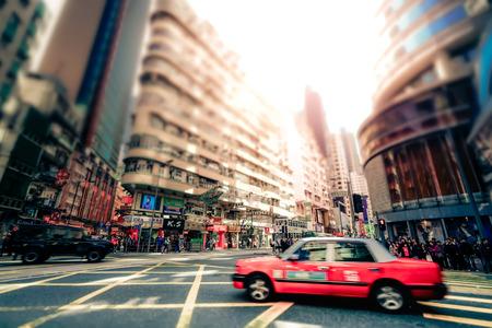 tilt shift: HONG KONG - JAN 15, 2015: Hong Kong cityscape view with city transport and plenty bright advertisements, billboards on skyscrapers facades. Tilt shift lens blur