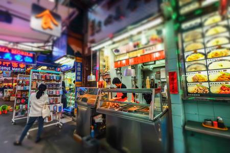 tilt views: HONG KONG - JAN 15, 2015: Selling take away asian food in traditional open-air street shop. Hong Kong city street life. Tilt shift lens blur