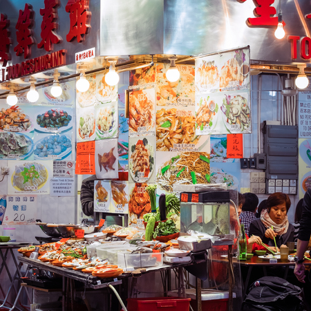 street life: HONG KONG - JAN 18, 2015: Local people and tourists enjoying eating asian food in traditional open-air restaurants. Hong Kong city street life