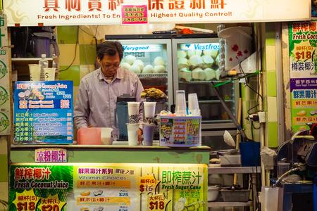 street life: HONG KONG - JAN 18, 2015: Unidentified local man selling fresh juice and coconut drink  at traditional open-air street shop. Hong Kong city street life