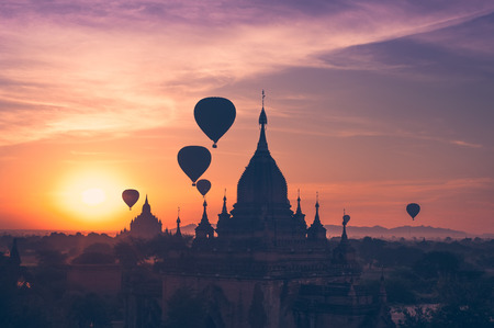 Amazing misty sunrise colors and balloons silhouettes over ancient Buddhist Temples at Bagan Kingdom. Myanmar (Burma). Travel landscapes and destinations Stock Photo