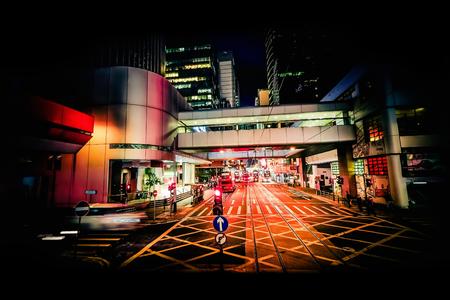 ciudad moderna vista nocturna abstracta con el movimiento de transporte, poca gente y los rascacielos iluminados. Hong Kong