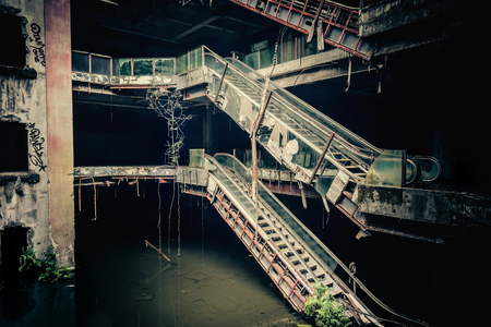 apocalyptic: Dramatic view of damaged escalators in abandoned shopping mall sunken by rain flood waters. Apocalyptic and evil concept