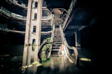 centro comercial: La extraordinaria vista de las escaleras mecánicas dañadas en el centro comercial abandonado hundida por las aguas de inundación lluvia. concepto apocalíptico y el mal