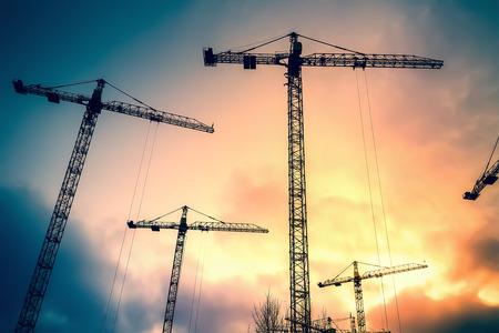 herramientas de construccion: Fondo industrial abstracto con las siluetas de las gr�as de construcci�n sobre el cielo impresionante puesta de sol