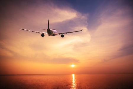 飛行機が夕日で素晴らしい熱帯の海の上を飛んでします。タイ旅行風景や目的地