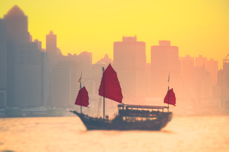 tilt: Tilt shift blur effect. Sunset skyline of Hong Kong with traditional cruise sailboat at Victoria harbor Stock Photo
