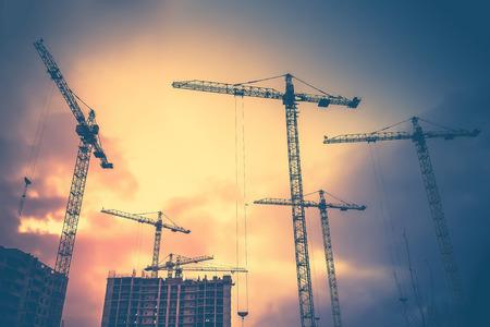 Zusammenfassung Industrielle Hintergrund mit Baukränen Silhouetten über erstaunliche Sonnenuntergang Himmel