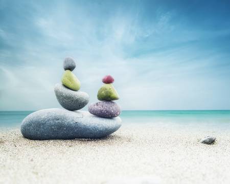 human pyramid: Balancing colorful zen stones pyramid on sandy beach under blue sky. Beautiful nature and spiritual concept