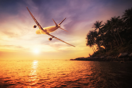 destinations: Airplane flying over amazing tropical sunset landscape. Thailand travel destinations