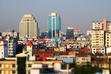 city buildings: Tilt shift blur effect. Futuristic aerial view panorama of developing Yangon city. Myanmar (Burma)