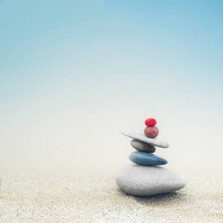 zen: Balancing colorful zen stones pyramid on sandy beach under blue sky. Beautiful nature and spiritual concept