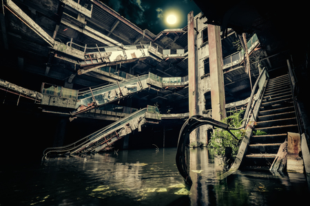 Dramatic view of damaged escalators in abandoned building. Full moon shining on cloudy night sky through collapsed roof. Apocalyptic and evil concept