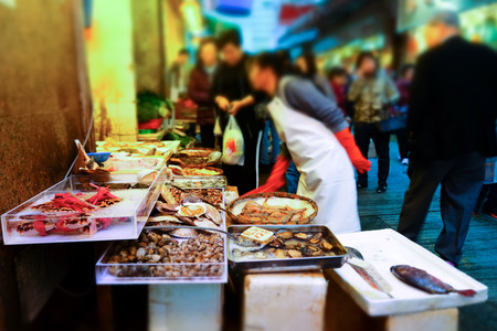 city fish market: Tilt shift blur effect. People buy seafood on the traditional asian street market. Hong Kong city street life