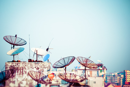 dish disk: Tilt shift blur effect. Abstract Yangon cityscape with parabolic satellite dishes at building roofs. Myanmar (Burma) travel landscapes and destinations