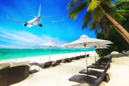 熱帯のビーチのヤシの木、白い砂浜とターコイズ ブルーの海の波の上を飛ぶ飛行機。ボラカイ島、フィリピン旅行