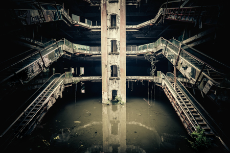 abandoned: Dramatic view of damaged escalators in abandoned shopping mall sunken by rain flood waters. Apocalyptic and evil concept
