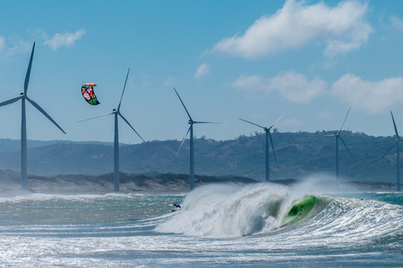 kite surfing: Amazing kite surfing at Philippines. Processional instructor surfing in ocean waives near windmills