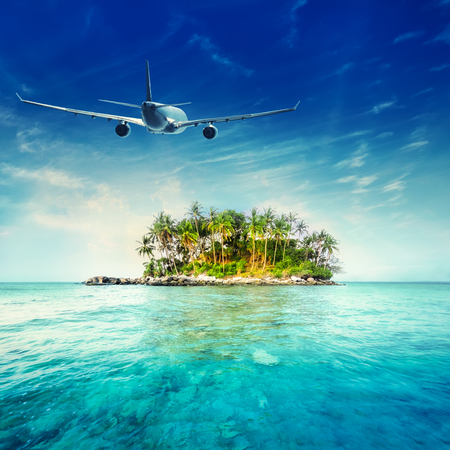 flight: Airplane flying over amazing ocean landscape with tropical island. Thailand travel destinations