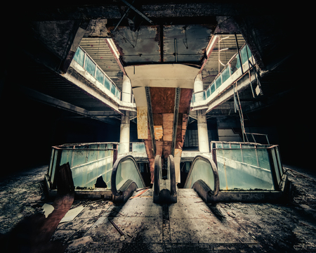 Dramatic view of damaged escalators in abandoned building. Apocalyptic and evil concept Stock Photo