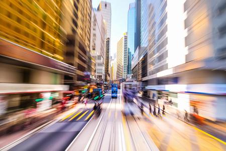 Moviéndose a través de la calle de la ciudad moderna con rascacielos. Hong Kong. Resumen de fondo paisaje urbano borrosa con siluetas de personas en el cruce de cebra y el tranvía azul. Acuarela efecto de la pintura, el desenfoque de movimiento