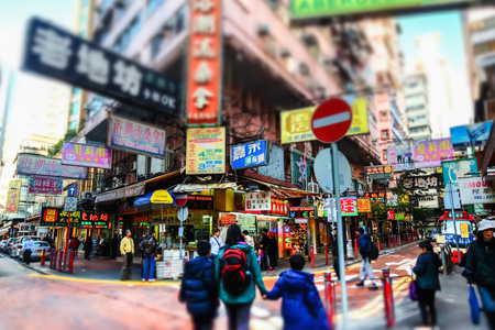 tilt and shift: HONG KONG - JAN 15, 2015: Tilt shift lense blur effect. Hong Kong cityscape view. People walking on crossroad at crowded streets with skyscrapers and shopping malls