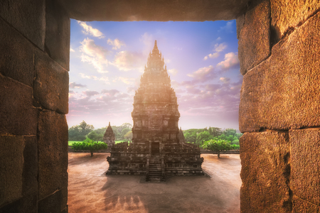 Beautiful buildings of ancient Prambanan or Rara Jonggrang Hindu temple complex against shining morning sun on background. Java, Indonesia. Amazing touristic landmark at sunrise